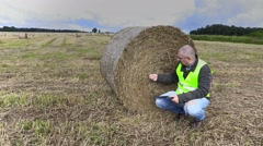 Farmer on field checking the straw bale Stock Footage