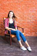 Cute woman with long legs sitting in the armchair behind a brick wall Stock Photos