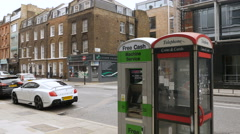 London street with Bentley, phone booth, pedestrians Stock Footage