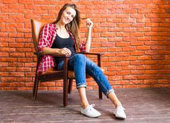 Cute woman with long legs sitting in the armchair behind a brick wall - stock photo