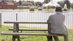 4K Sad senior man sitting in park alone with his thoughts Stock Footage