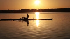 Rower / skuller gets exercise with the sun just over the horizon Stock Footage