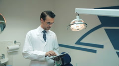 Dentist using tablet at the dental clinic Stock Footage