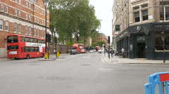 Vivid London intersection with red busses and cyclists and pedestrians Stock Footage