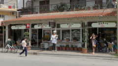People sit and eat in front of bakery, cars passing down the street by Sheyno. Stock Footage