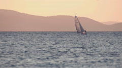 4K Sailboat on the horizon in the open sea at dusk Stock Footage