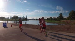 Pan of Group of runners passing by view of Dallas skyline reflecting in lake Stock Footage