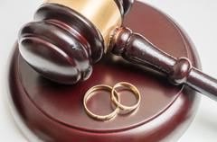 Divorce concept. Closeup view on gavel and wedding rings. Kuvituskuvat