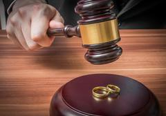 Divorce concept. Hand of judge in courtroom is holding gavel. Wedding rings i - stock photo