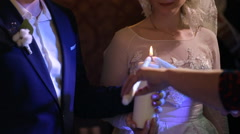 Bride and groom are holding a burning candle Stock Footage