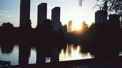 Silhouettes of people walking near beautiful city lake at sunset, summer evening Stock Footage