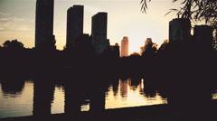 Last minutes of sunset, dark silhouettes of people walking near city lake Stock Footage