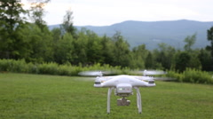 A drone or quadcopter hovering and taking off in a backyard surrounded by Stock Footage