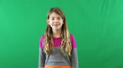A preteen girl looking at the camera and smiling in front of a green screen Stock Footage