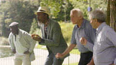 4K Happy senior male friends bowling & laughing together in the park Stock Footage