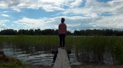 Woman standing on a dock Stock Footage