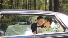 Man and woman in wedding dresses sit in limousine together Stock Footage
