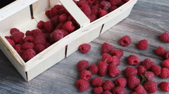 Fresh raspberry in pottle and bulk on a wooden table. Stock Footage
