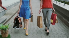 Legs slender young women walking down the street past the store with shopping Stock Footage