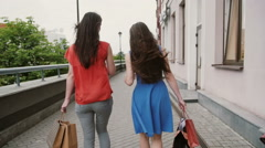 Back view of beautiful young women walking past the shops, with shopping bags Stock Footage