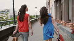 Two beautiful young woman friends walking with shopping bags, talking having fun Stock Footage