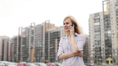 Girl Talking on the Phone While Standing on Street Parking on the Background of Stock Footage