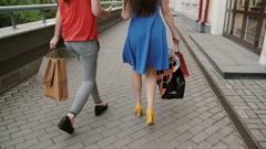 Two beautiful young woman friends walking with shopping bags, talking having fun Stock Footage