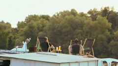 Two young men sitting on the roof of floating raft cafe on the river Stock Footage