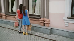Young girls friends standing near shop window with wedding dresses and discuss Stock Footage
