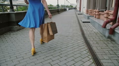 legs slender young woman, walking in the city past the store with shopping bags - stock footage