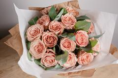 Capuchino grade roses. Florist girl with rich bunch flowers. Fresh spring Stock Photos
