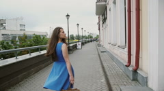 Wind blows long dark hair beautiful young woman walking down the street past the Stock Footage