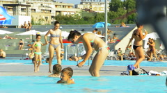 People sunbathing and swimming in the public outdoor pool Stock Footage