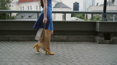 Legs slender young woman, walking in the city down the street with shopping bags Stock Footage