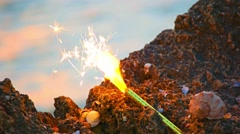 Sparcler candle and spiral shell on the rocky coast of sea Stock Footage