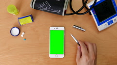 Top shot of man using iphone with various hand gestures on green screen Stock Footage