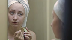 Beautiful woman plucking her eyebrows in front of mirror Stock Footage