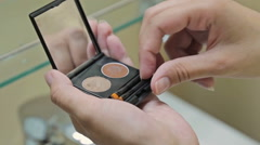 Woman is brushing eye shadow palette cosmetic Stock Footage