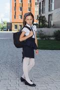 Cute schoolgirl in uniform standing in campus Stock Photos