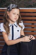 Schoolgirl in uniform waiting for the bus to school Stock Photos