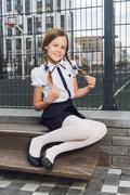 Cute schoolgirl in uniform at playground Stock Photos