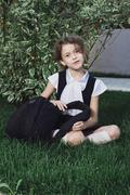 Cute elementary schoolgirl in uniform sitting with backpack on grass Stock Photos