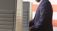 Man voting in a voting booth, pan up shot Stock Footage