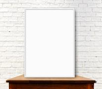 White frame mock up on the wood table at white brick wall Stock Photos
