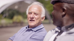 4K Happy senior male friends chatting & laughing in the park on a sunny day Stock Footage