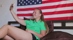 Unated states flag. Beautiful girl use a smartphone makes photo Stock Footage