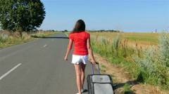 4K.   Woman  in red  blouse with  suitcase  go on  road Steady shot Stock Footage