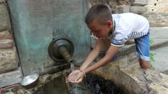 Boy drinking water from hands from ancient oriental tap in the old city of Ne Stock Footage