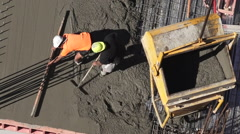 Construction site workers leveling cement in building site. Stock Footage