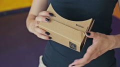 Young curly woman using Virtual Reality Glasses. Google cardboard Stock Footage
